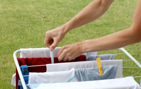 Laundry hanging on the clothesline, hands cliping laundry pegs