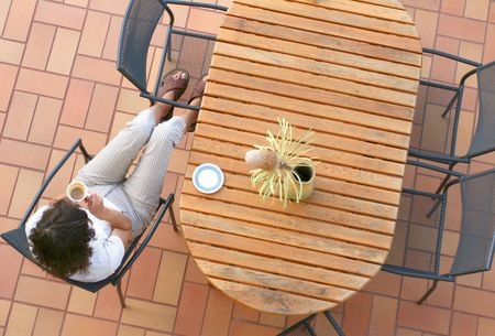 Young girl sitting on the terrace drinking coffee, unusual point of view