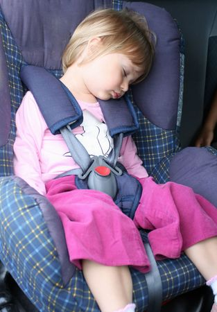 car seat: Young girl rests in the car seat
