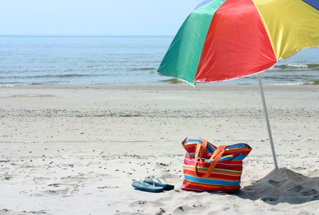 Beach bag,flipflop and umbrella against blue sea and sand