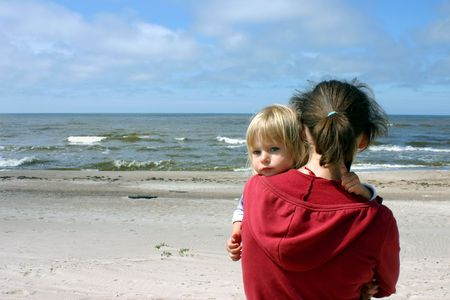 Mother with little daughter on her hands standing by the sea  Stock Photo