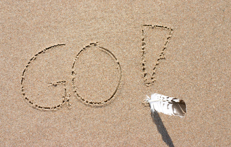 urge: Slogan GO written on sand with exclamation mark and real feather