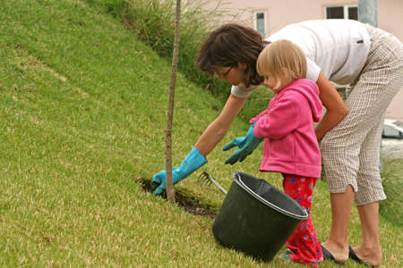 Mother and her 2-3 years old daughter gardening