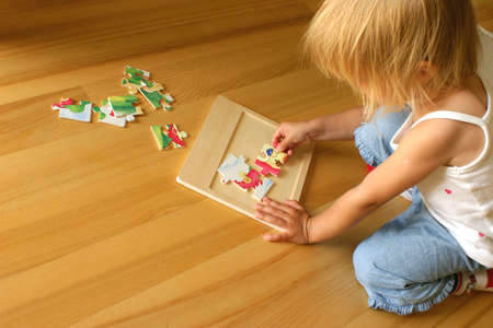 learning by doing: 2-3 years old girl kneeling on the floor and solving jigsaw puzzle