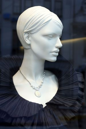 Luxury mannequin dreesed in elegant black evening dress on display with reflections on the shop window