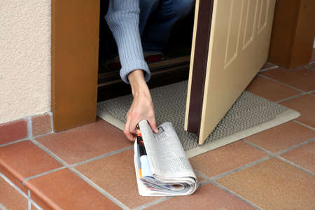 front stoop: Woman picking up morning paper through the open door Stock Photo