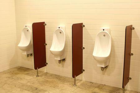 Three men urinals in the public restroom photo