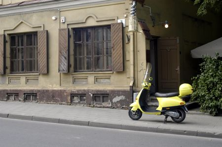 Yellow motor scooter left in front of the cafe entrance                                 photo