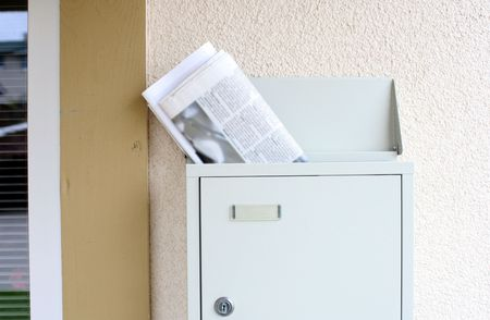 Morning newspaper and magazine sticking out of mailbox. Newspaper text blured intentionaly Stock Photo