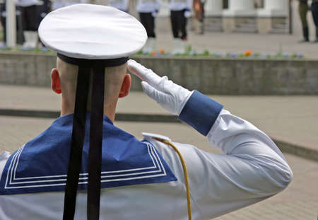 solemnity: Navy soldier salutes at the lithuanian national flag ceremony Stock Photo