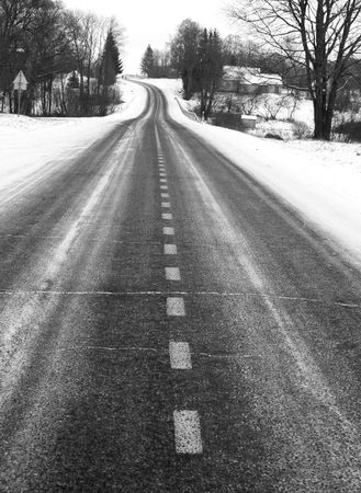 dividing: Black and white picture of the country road in winter, focus on dividing line