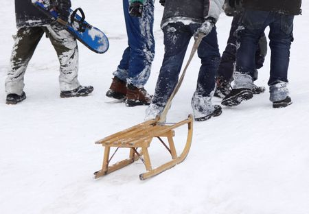 Boys climbing up the snowy hill with sledge and snowboard, focus on sledge photo