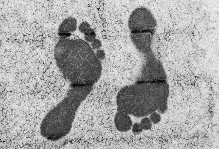 Two opposite barefoot footprints on snow at winter Stock Photo