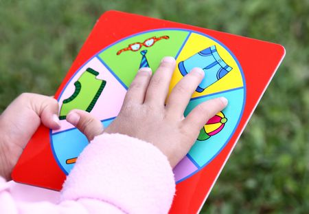 Little child playing learning game. Focus on hand and game table