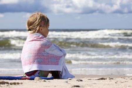 Ni�a sentada en la playa y mirando el mar Foto de archivo - 5494801