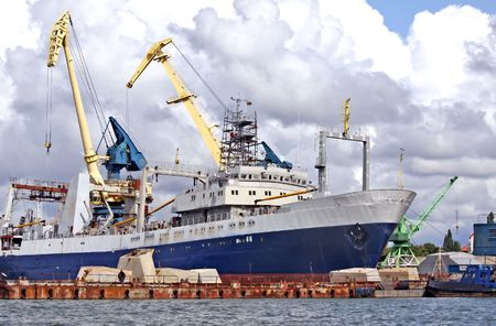 Cargo vessel standing at the trading seaport with cranes and warehouses Stock Photo