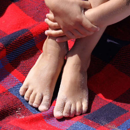 beach mat: Little girls sandy feet on red beach mat