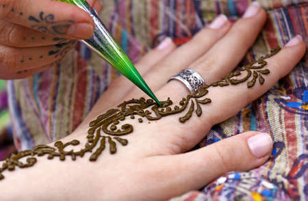 Picture of human hand being decorated with henna tattoo photo