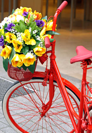 Red painted bicycle with a bucket of colorful flowers  Фото со стока
