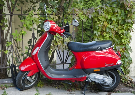 chaining: Vilnius, Lithuania - October 06,  2011: Red Vespa scooter standing in natural urban environment
