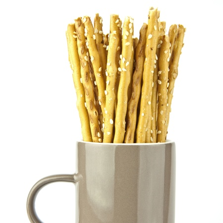 Crispy bread sticks put in mug isolated on white photo
