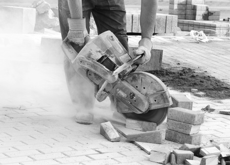 Black and white picture of worker with concrete saw in his hands and working photo
