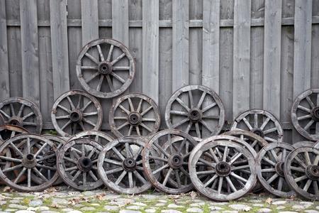 carreta madera: Manojo de viejas ruedas de los carros de madera contra la cerca de madera Foto de archivo