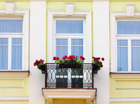 old building facade: Three house windows and balcony with flowers