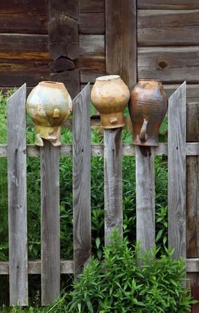 Old broken jars on the wooden fence photo