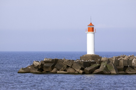 White lighthouse and stone pier in Ventspils, Latvia photo
