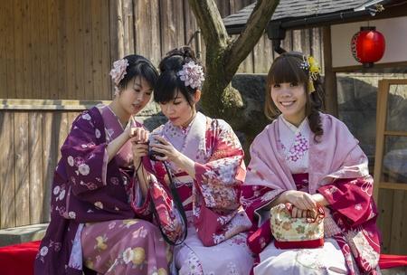 kyoto: Kyoto, Japan - March 27, 2012: Modern japanese girls in traditional kimono enjoying themselves near Kiyomizu-dera Buddhist temple in eastern Kyoto