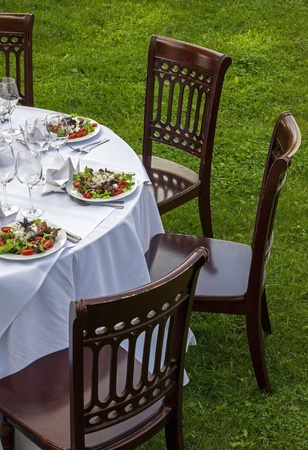 Table setting with chairs for garden banquet  photo