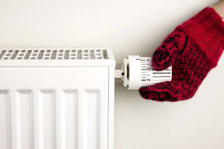 heat home: Single human hand with knitted glove turning radiator thermostat Stock Photo