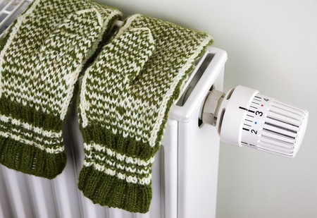 Pair of green knitted gloves drying on the radiator with thermostat Stock Photo - 16852304