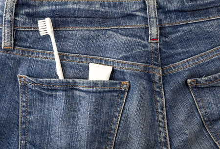 Toothbrush and toothpaste in the back pocket of blue jeans
