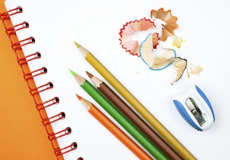 Four colorful pencils with sharpener and shavings on white notebook photo