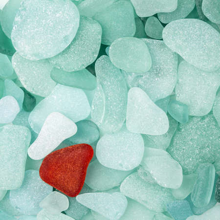 unique  difference: Unique red sea glass isolated on green sea glass background