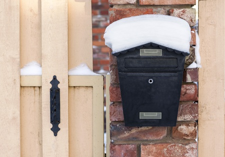 Black mailbox covered with snow outside residential house photo