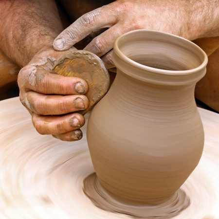 Close-up on potters hands making clay pottery photo