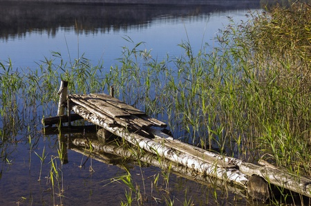desolation: Old lake pier early in the morning Stock Photo
