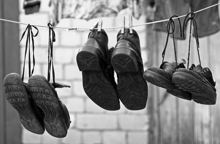 Three pairs of old shoes hanging on clothesline Stock Photo