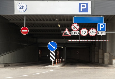car park: Entrance to the underground parking lot with multiple warning road signs Stock Photo