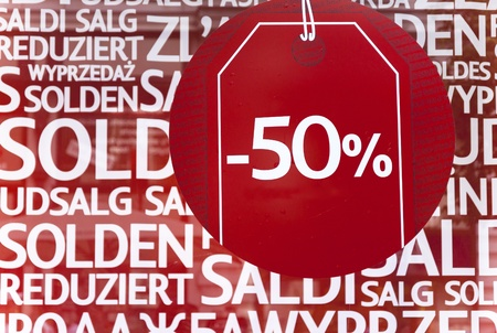 multilingual: Shop window display with text Sale in different languages on red poster and focus on 50 per cent discount text Stock Photo