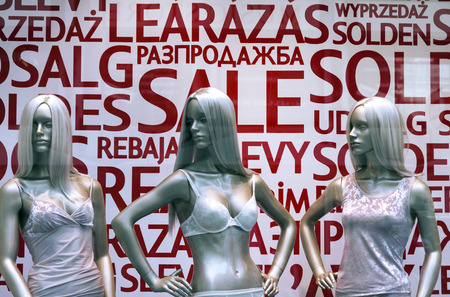 Shop window display with three mannequins in lingerie and text Sale in different languages on the background photo