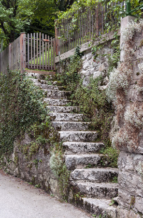 Old stone stairs leading to wooden gate entrance photo