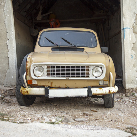 abandoned car: Front view of an old abandoned car against shabby environment