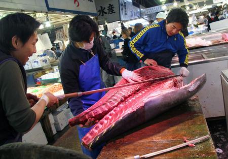 butcher s shop: TOKYO, JAPAN-APRIL 5, 2012  Three workers slicing tuna in Tokyo Tsukiji fish market, Japan