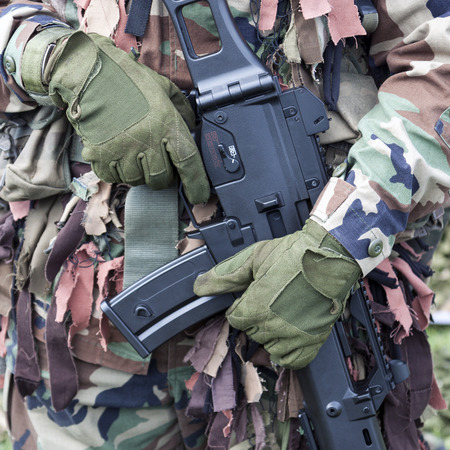 Hands of a soldier in camouflage uniform holding weapon photo