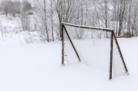 goalpost: Old abandoned wooden soccer goal covered with snow during winter season