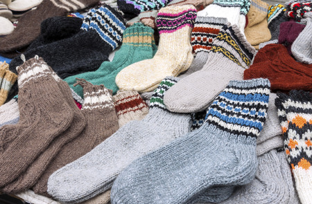 warm clothes: Bunch of handmade colorful woolen socks on the market Stock Photo